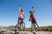 Fit cyclist couple cheering at the summit — Stock Photo