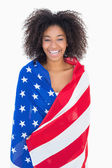 Pretty girl wrapped in american flag smiling at camera — Foto Stock
