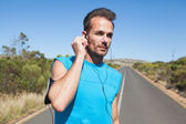 Athletic man adjusting his earphones on a run — Stock Photo