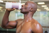 Sporty man drinking protein in gym — Stock Photo