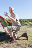 Happy camper setting up his tent — Stockfoto