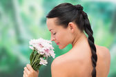 Beautiful nude brunette smelling bunch of pink flowers — Stock Photo