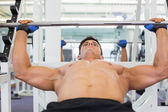 Shirtless muscular man lifting barbell — Stock Photo