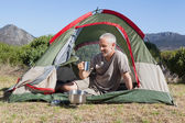 Happy camper holding mug outside his tent — Foto Stock