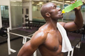 Muscular man drinking energy drink in gym — Stock Photo