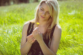 Pretty blonde in sundress holding yellow flower — Stockfoto