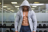 Muscular young man in hood jacket — Stock Photo