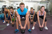 Muscular instructor leading kettlebell class — Stock Photo