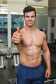Shirtless muscular man giving thumbs up in gym — Stock Photo