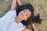 Casual pretty woman napping on the grass — Stock Photo