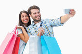 Attractive young couple with shopping bags taking a selfie — Stock Photo