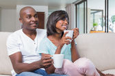 Happy couple relaxing on the couch having coffee — Stock Photo