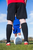 Football players facing off on pitch — Stockfoto