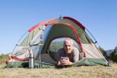 Happy camper smiling at camera lying in his tent — Stockfoto