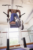 Male body builder doing pull ups at the gym — Stockfoto