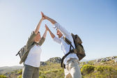 Hiking couple high fiving on mountain terrain — Stock Photo
