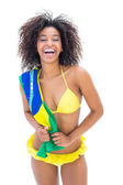 Fit girl in yellow bikini holding brazil flag — Stock Photo