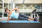 Fit brunette doing pilates on exercise mat — Foto de Stock