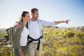 Hiking couple pointing and smiling on country terrain — Stock Photo