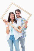 Happy young couple holding picture frame — Stock Photo