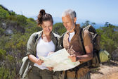 Happy hiking couple standing on mountain trail looking at map — Stock Photo