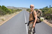 Handsome hiker walking on road and smiling at camera — Stock Photo