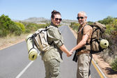 Hitch hiking couple standing holding hands on the road — Stock Photo