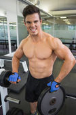 Shirtless young muscular man lifting weight in gym — Stock Photo