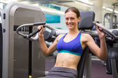Fit smiling brunette using weights machine for arms — Stock Photo