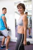 Fit couple lifting weights together smiling at camera — Photo