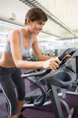 Smiling brunette working out on the cross trainer — Stock Photo