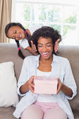 Pretty mother holding gift with her daughter revealing — ストック写真