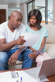 Worried couple calculating bills on the couch — Stock Photo
