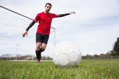 Goalkeeper in red kicking ball away from goal — Foto de Stock