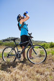 Fit cyclist riding in the countryside taking a drink — Foto de Stock