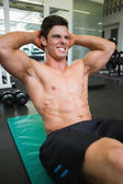 Determined muscular man doing abdominal crunches — Stok fotoğraf