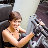 Focused brunette using weights machine for arms — Stock Photo