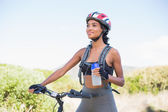 Fit woman going for bike ride holding water bottle — Stock Photo