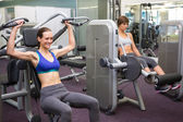 Healthy brunette using weights machine for arms — Stock Photo