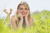 Pretty blonde in sundress lying on grass smiling at camera — Zdjęcie stockowe