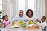 Happy family smiling at camera at lunch — Stock Photo