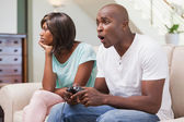 Bored woman sitting next to her boyfriend playing video games — Stock Photo