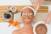 Peaceful brunette getting a mud treatment facial — Stock Photo
