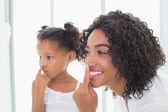 Pretty mãe colocar creme de rosto com sua filha — Foto Stock