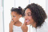 Pretty mother putting face cream on with her daughter — Stock Photo