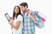 Attractive young couple with shopping bags and tablet pc — Stock Photo