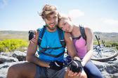 Cyclist couple taking break on rocky peak — Stock Photo