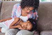 Cute daughter sleeping across mothers lap on the sofa — Stockfoto
