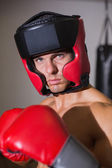Male boxer in defensive stance in health club — Stockfoto