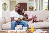 Happy couple relaxing on the couch with breakfast — Stock Photo